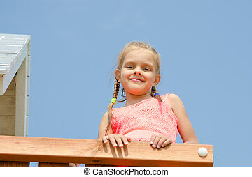 Happy girl climbed on the playground and looked down smiling