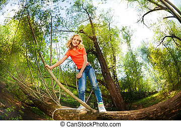 Happy girl climbing over fallen tree in the forest
