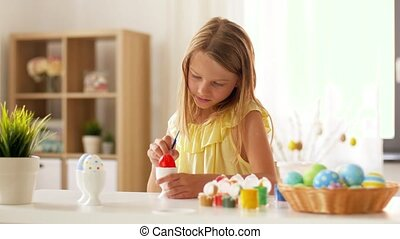 happy girl coloring easter eggs at home - easter, holidays...