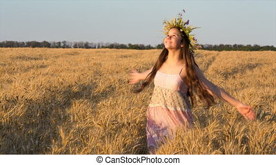 Happy girl dancing on golden wheat field and touching ripe ears