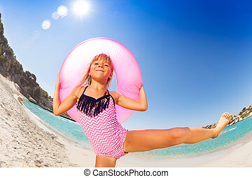 Happy girl dancing with rubber ring on the beach