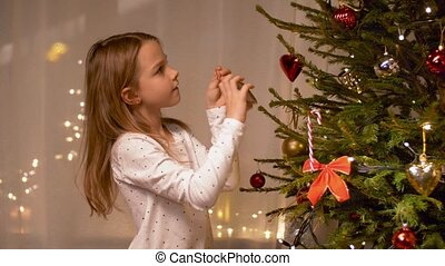 happy girl decorating christmas tree at home - winter...