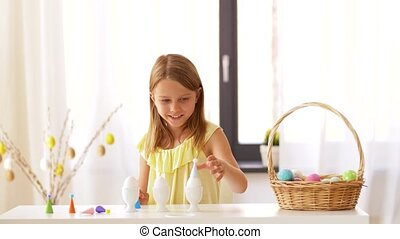 happy girl decorating easter eggs at home - easter, holidays...