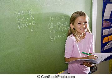 Happy girl doing math on blackboard in class