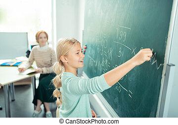 Happy girl doing sums near the school board.
