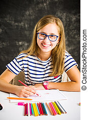 Happy girl drawing with colorful pencils