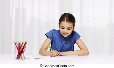 happy girl drawing with colour pencils at home