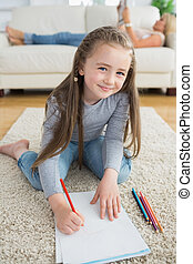 Happy girl drawing with her mother reading newspaper
