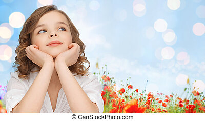 happy girl dreaming over poppy field background