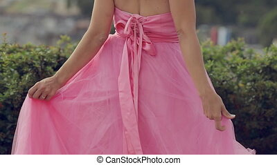 Happy girl dressed in a pink fluffy dress looking at the...