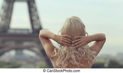 Happy girl dressed in a pink fluffy dress looking at the Eiffel Tower in Paris