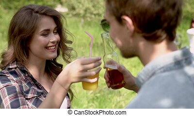 Happy girl drinks outdoors with her male friend