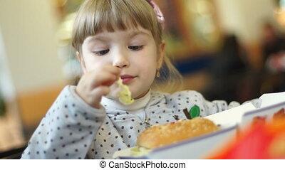 Happy girl eating a big burger