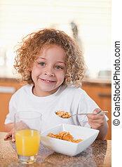 Happy girl eating cereals for breakfast