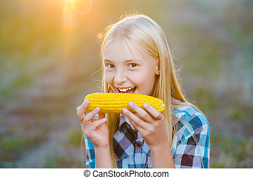 Happy girl eating healthy corn on the cob