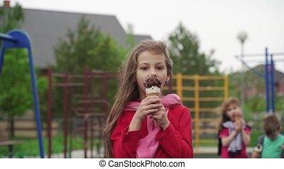 Happy girl eating ice-cream outdoors on children playground...