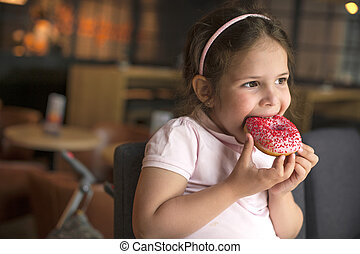 happy girl eating pastry at a cafe. Harmful sweet food. Trends in food. Copy space