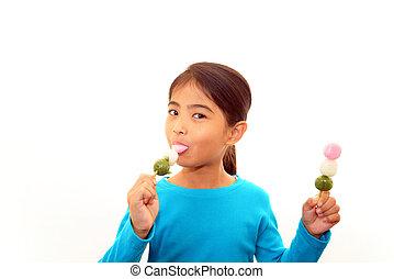 Happy girl eating sweets