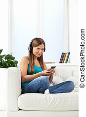 Happy girl enjoying music on mp3 player. beautiful brunette girl sitting on sofa at home
