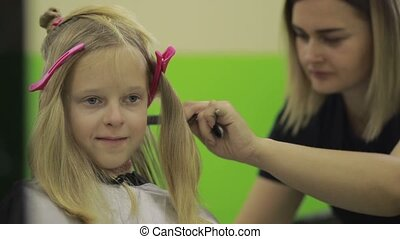 Happy girl getting a new haircut by hairdresser