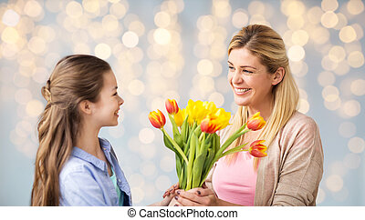happy girl giving flowers to mother over lights