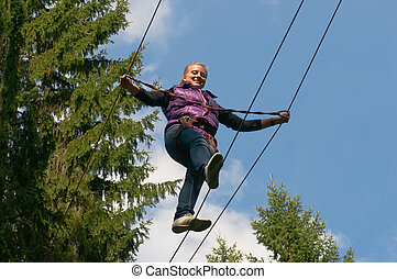 Happy girl goes on a rope against the blue sky