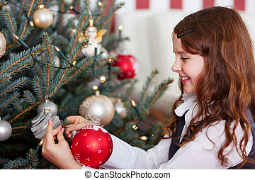 Happy girl hanging Christmas baubles