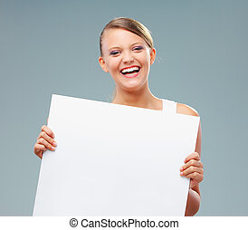 Happy blonde girl holding up a blank banner, copy space