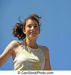 Happy teenage girl against the blue sky