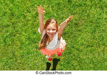 Happy girl having fun jumping on the green grass