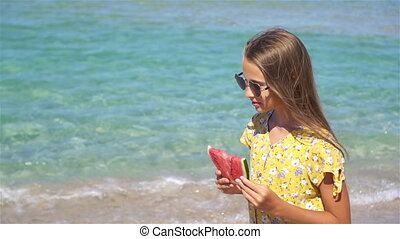 Girl relaxing on the beach with a slice of watermelon in her hand