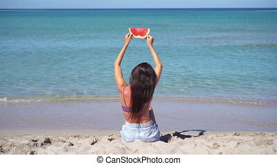 Woman relaxing on the beach on a summer day with a slice of watermelon in her hand