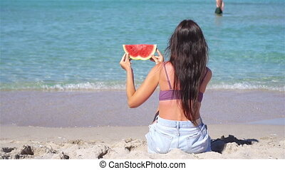 Woman relaxing on the beach with a slice of watermelon in her hand