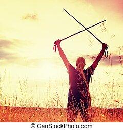 Happy girl  hiker with crossed poles in evening golden meadow