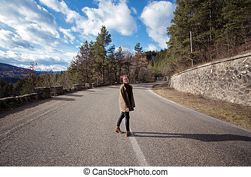 girl hipster stands on a mountain road