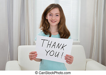 Happy Girl Holding Board With The Text Thank You At Home