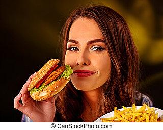 Happy girl holding fastfood hamburger and fried potatoes .