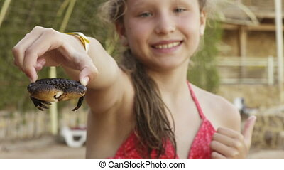 Happy girl holding showing a crab on a beach