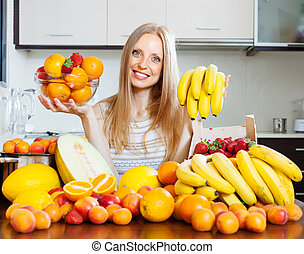 Happy girl holding various fruits in home kitchen