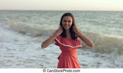 Happy girl in a dress on one shoulder walking along oceanfront
