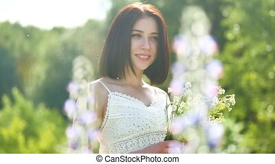 happy girl in a field with flowers in nature. girl in a field smiling woman holding a bouquet of outdoor flowers