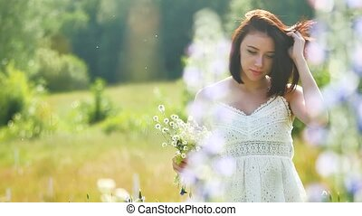 happy girl in a field with flowers in nature. girl in a field smiling woman holding a bouquet of flowers outdoor
