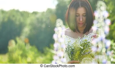 happy girl in a field with flowers in nature. girl in a field smiling woman holding a bouquet outdoor of flowers