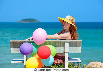 Happy girl in a hat sitting on a background of the azure sea.