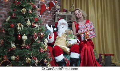 Happy girl in a long red dress sitting beside Santa with gifts