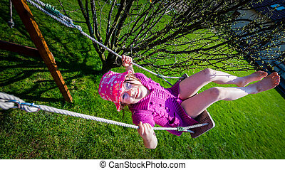 Happy girl in a pink hat having fun on a swing outdoor