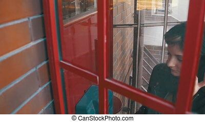 Happy Girl in a Red Telephone Booth Talking on the Phone in the Street