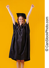 Happy girl in academic dress holding up his hands