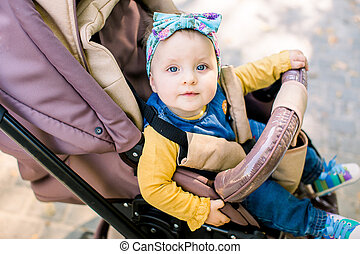 Happy girl in baby carriage playing in pram on background nature. Portrait cute little beautiful girl of 9 months sitting or stroller and waiting for mom.