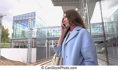 Happy girl in blue coat talking on her mobile phone at train station. 4K shot